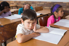 Bored pupil sitting at his desk Royalty Free Stock Photo