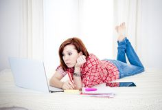 Bored red hair student, business woman lying down working on laptop. Bored red hair student or business woman lying down working on her computer wearing a red Stock Photo