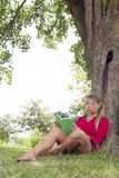Bored 20s girl reading a summer book under a tree. Outdoors reading - bored young suntanned blond woman questioning her summer book,reading on a giant stone in Stock Images