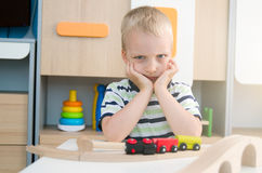 Bored sad little boy sitting at table Royalty Free Stock Photo
