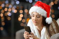 Bored or sad woman checking phone in christmas royalty free stock photography