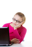 Bored, sad woman sitting in front of laptop. Royalty Free Stock Photos