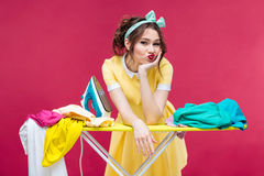Bored sad young woman ironing clothes Royalty Free Stock Photography