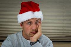 Bored santa. Young man wearing a santa hat  with a bored expression Stock Image
