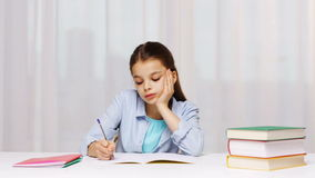 Bored school girl with books and notepad at home stock footage