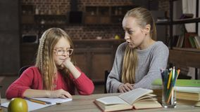 Bored girl unwilling to do homework with mother. Bored school girl in eyeglasses unwilling to do her homework while studying together with her mother at home stock video footage