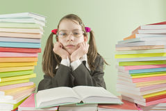 Bored school girl sitting at the table. With stacks of books Stock Photos