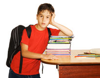 Bored schoolboy. Schoolboy moping on a stack of homework books Royalty Free Stock Photos