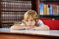 Bored Schoolboy Leaning On Table In Library Royalty Free Stock Photo