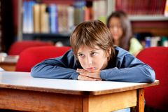 Bored Schoolboy Looking Away. Bored little schoolboy looking away while leaning on table in library with female classmate in background royalty free stock image