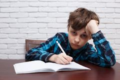 Bored schoolboy writing down a task into a notebook. Studying di. Fficulties, school life, education concept royalty free stock images