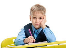 Bored schoolboy writing Royalty Free Stock Image