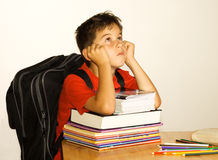 Bored schoolchild. Schoolboy moping on a stack of homework books Royalty Free Stock Photos