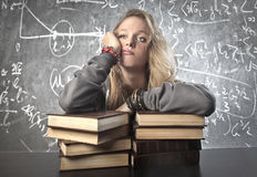 Bored Schoolgirl. A schoolgirl is bored by the study stock photography