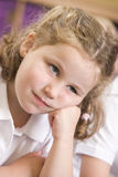 Bored schoolgirl sitting in primary class royalty free stock image