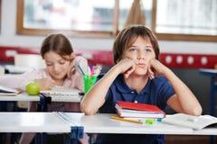 Bored Schooljongen die weg Aanwezig zijnd Bureau bekijken royalty-vrije stock afbeelding