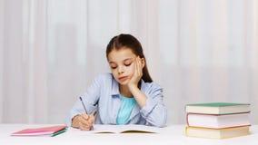 Bored schoolmeisje met boeken en blocnote thuis stock footage