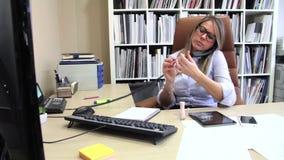 Bored secretary polishing nails and receiving calls stock video