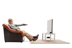 Bored senior changing channels on TV Royalty Free Stock Photos