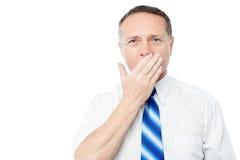 Bored senior executive yawning Stock Image