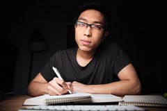 Bored serious man in glasses learning and writing. Bored serious asian young man in glasses learning and writing in the evening at home Stock Photos
