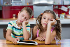 Bored siblings with digital tablet in kitchen Stock Image