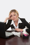 Bored and sick of work. Attractive blond woman sitting at desk in front of computer with box of kleenex tissues looking ill Royalty Free Stock Images
