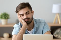 Bored sleepy man feels drowsy resting on hand near laptop. Bored sleepy man feels tired drowsy resting on hand near laptop, unmotivated lazy sluggish office royalty free stock photography