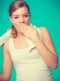 Bored sleepy woman yawning while holding towel Royalty Free Stock Photo