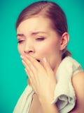 Bored sleepy woman yawning while holding towel Royalty Free Stock Photography