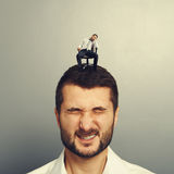 Bored small man sitting on the head Royalty Free Stock Photos