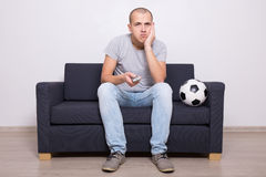 Bored soccer fan watching game on tv Royalty Free Stock Image
