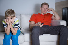 Bored son. Bored little son sitting with his father in living room Stock Images