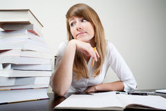 Bored student. Sitting at table with books Royalty Free Stock Photos