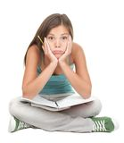 Bored student. University student bored, frustrated and overwhelmed by studying homework. Young woman sitting down on floor isolated on white background Royalty Free Stock Images