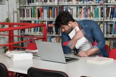 Bored Student With Books in Library. Male College Student Looks Tired While Studying With a Laptop and Textbooks in the Library Stock Image