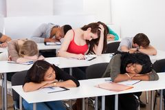 Bored student with classmates sleeping at desk Royalty Free Stock Photos