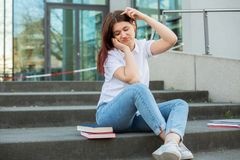 Bored student concept. Demotivated student sitting on campus stairs trying to study looking to camera. Bored student from learning thinking about what to do next stock photo