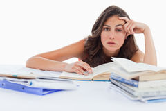 Bored student doing her homework. Against white background Royalty Free Stock Photography