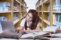 Bored student doing homework in library. Picture of female student looks bored while doing homework in the library Stock Photo