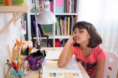 Bored student girl. Bored school girl doing homework at home. Looking at camera Royalty Free Stock Images