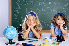 Bored student kids at school classroom in desk Royalty Free Stock Images