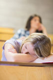 Bored student listening while classmate sleeping Stock Photography