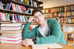 Bored student or young man with books in library Royalty Free Stock Photography