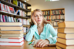 Bored student or young woman with books in library Royalty Free Stock Images