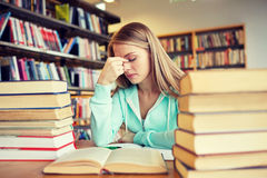 Bored student or young woman with books in library Stock Photos
