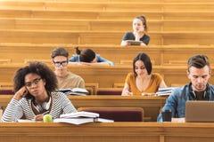 Bored studenten die aan spreker bij universiteit luisteren royalty-vrije stock foto's