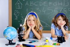 Bored studentenjonge geitjes bij schoolklaslokaal in bureau Royalty-vrije Stock Afbeeldingen
