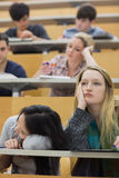 Bored students sitting in a lecture hall. Students feeling bored in a lecture hall in college Stock Photography