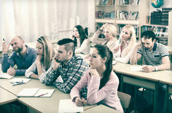 Bored students sitting at lesson. Bored adult students sitting at lesson in classroom Stock Photos